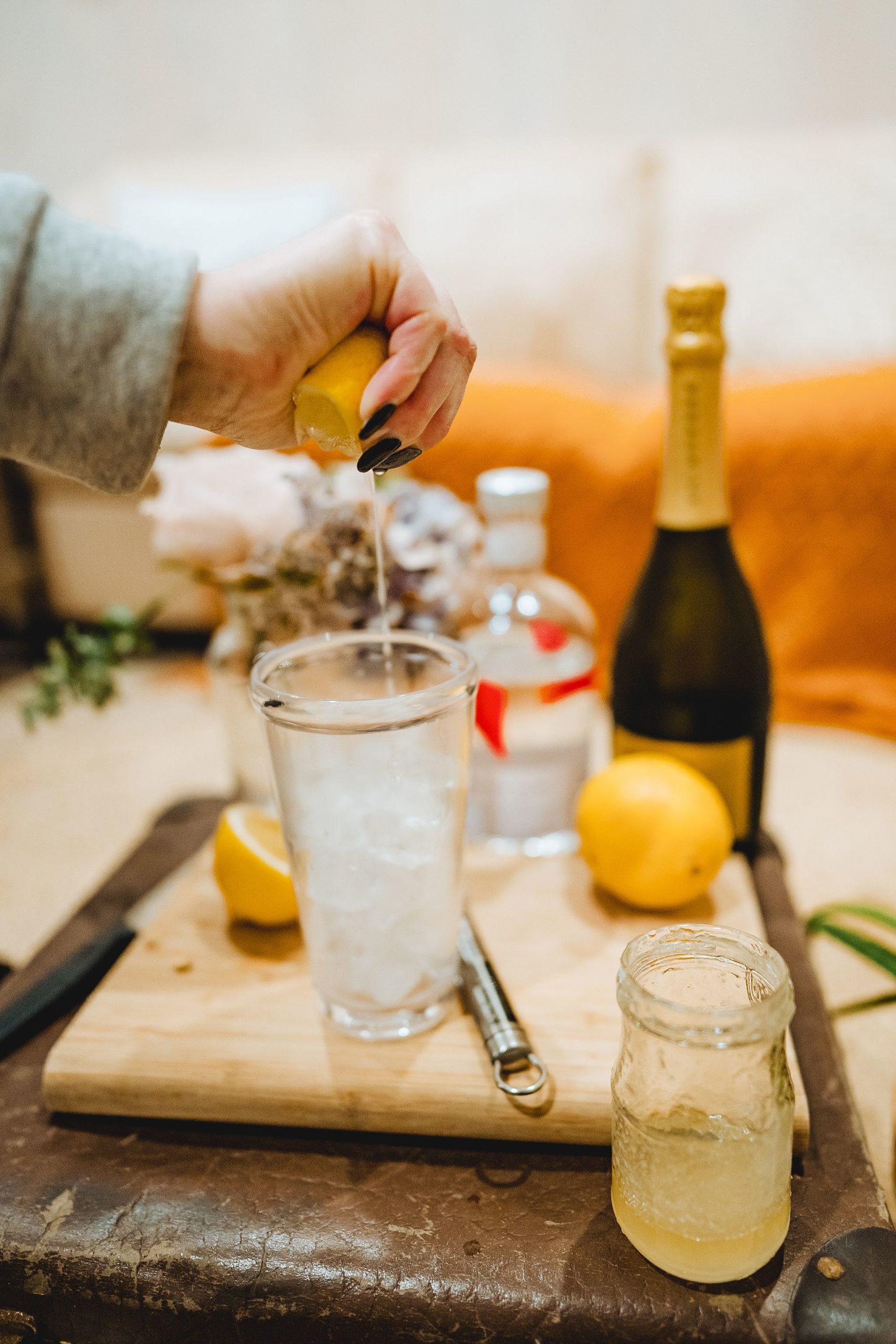 squeezing lemon into a cocktail