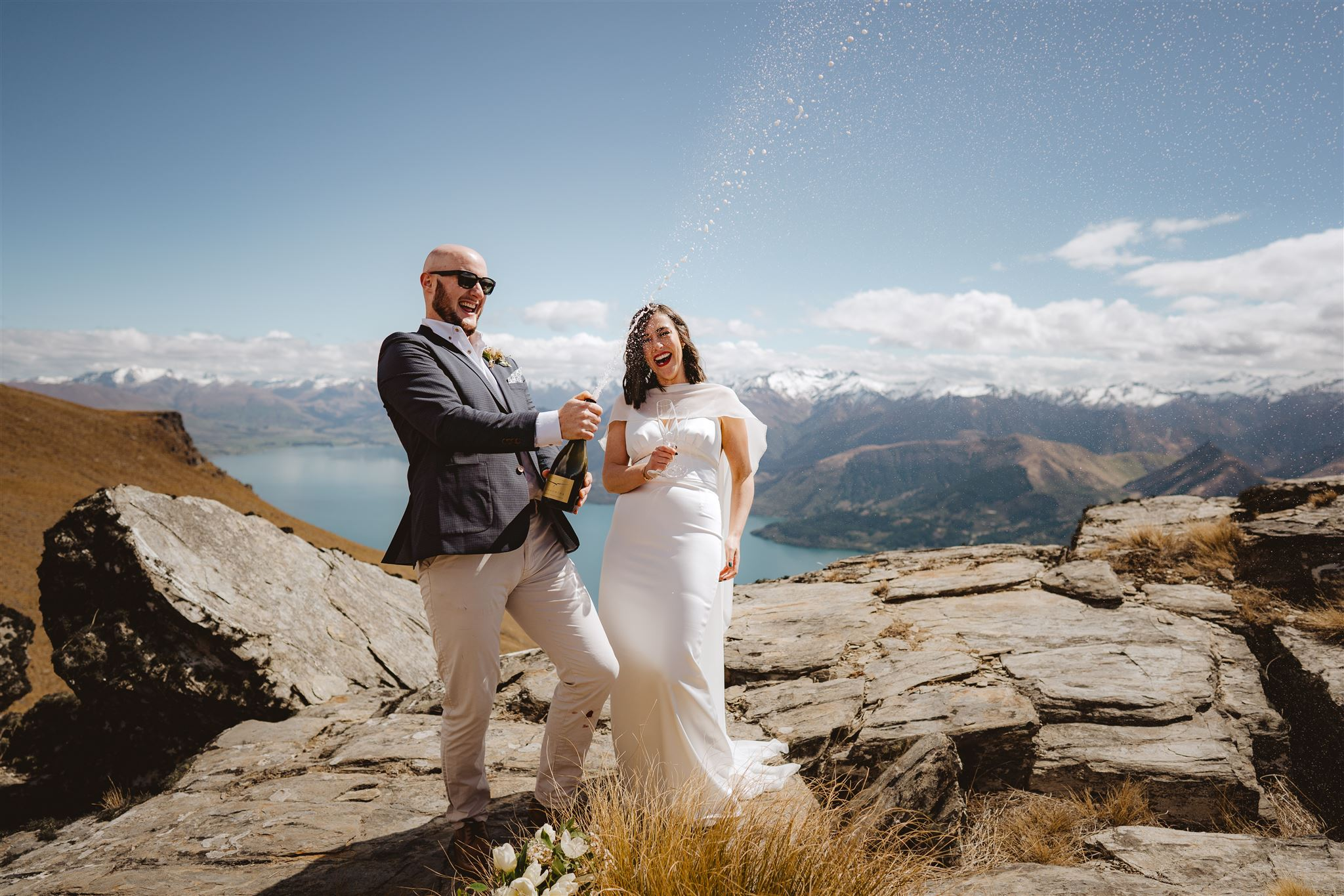 Bride and groom celebrating their wedding by spraying champagne on mountain top in Queenstown
