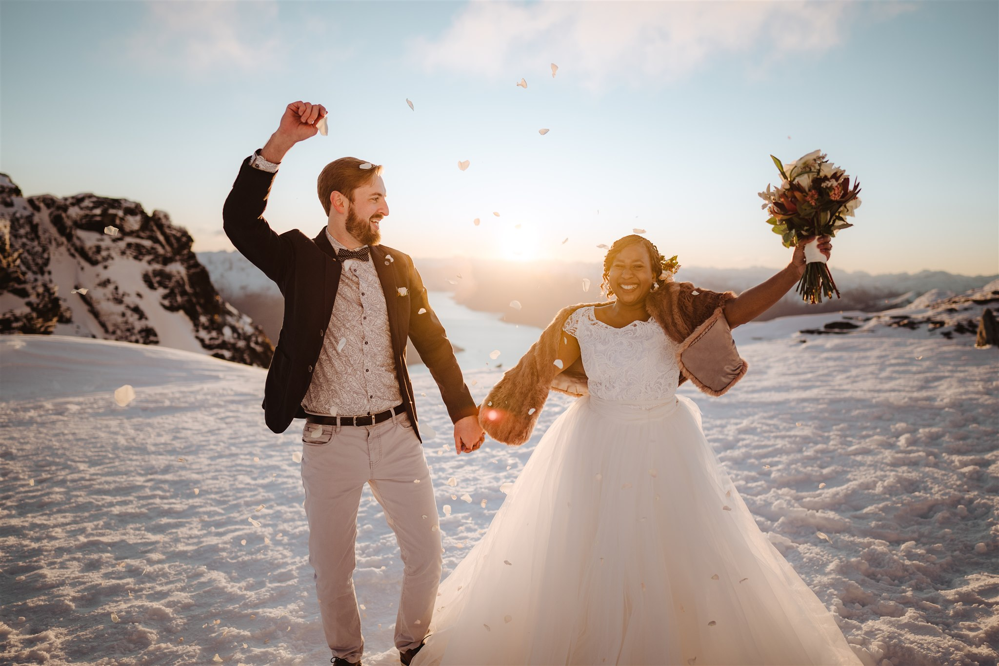 Bride and groom in wedding outfits on a mountain top in the snow celebrating their wedding with confetti and punching the air with bouquet