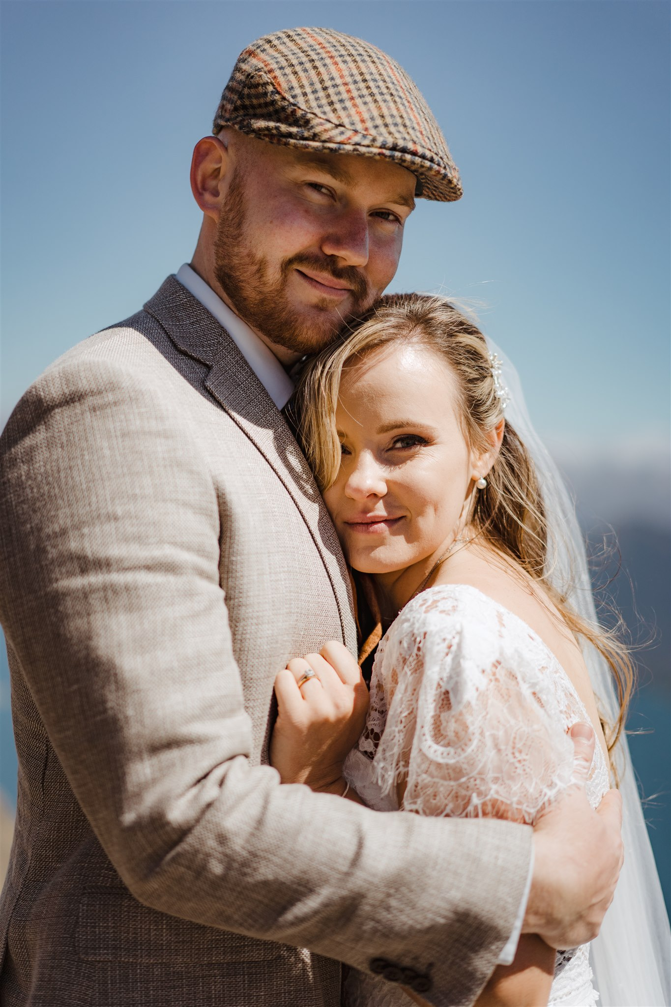 bride and groom cuddle and kiss on mountain top in Queenstown New Zealand in portrait