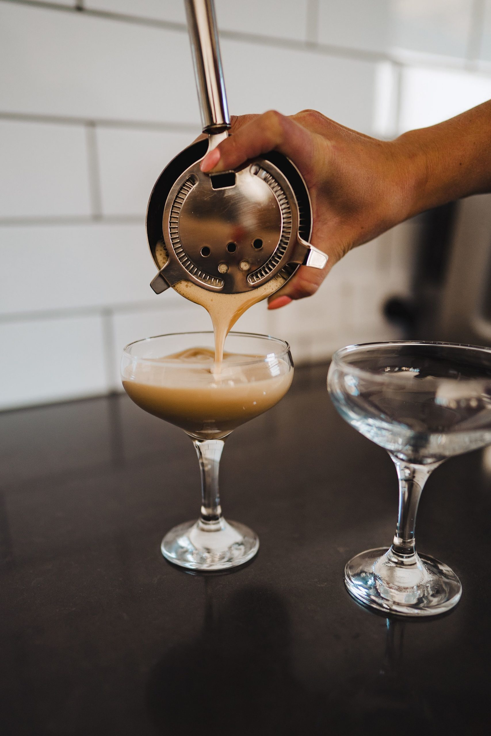pouring cocktail into martini glasses