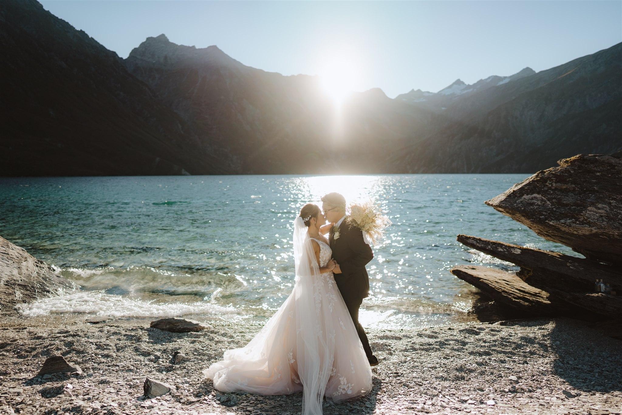 bride and groom cuddle and kiss beside Lochnagar in Queenstown