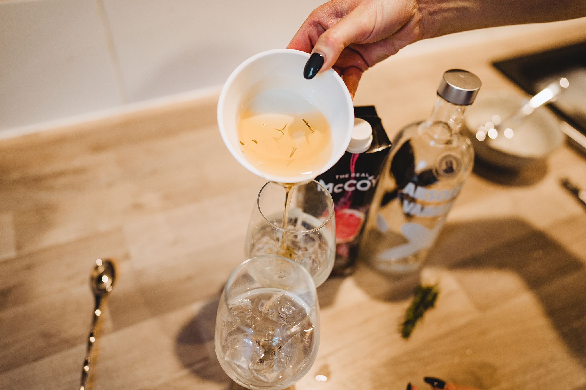 adding rosemary infused simple syrup to vodka cocktail