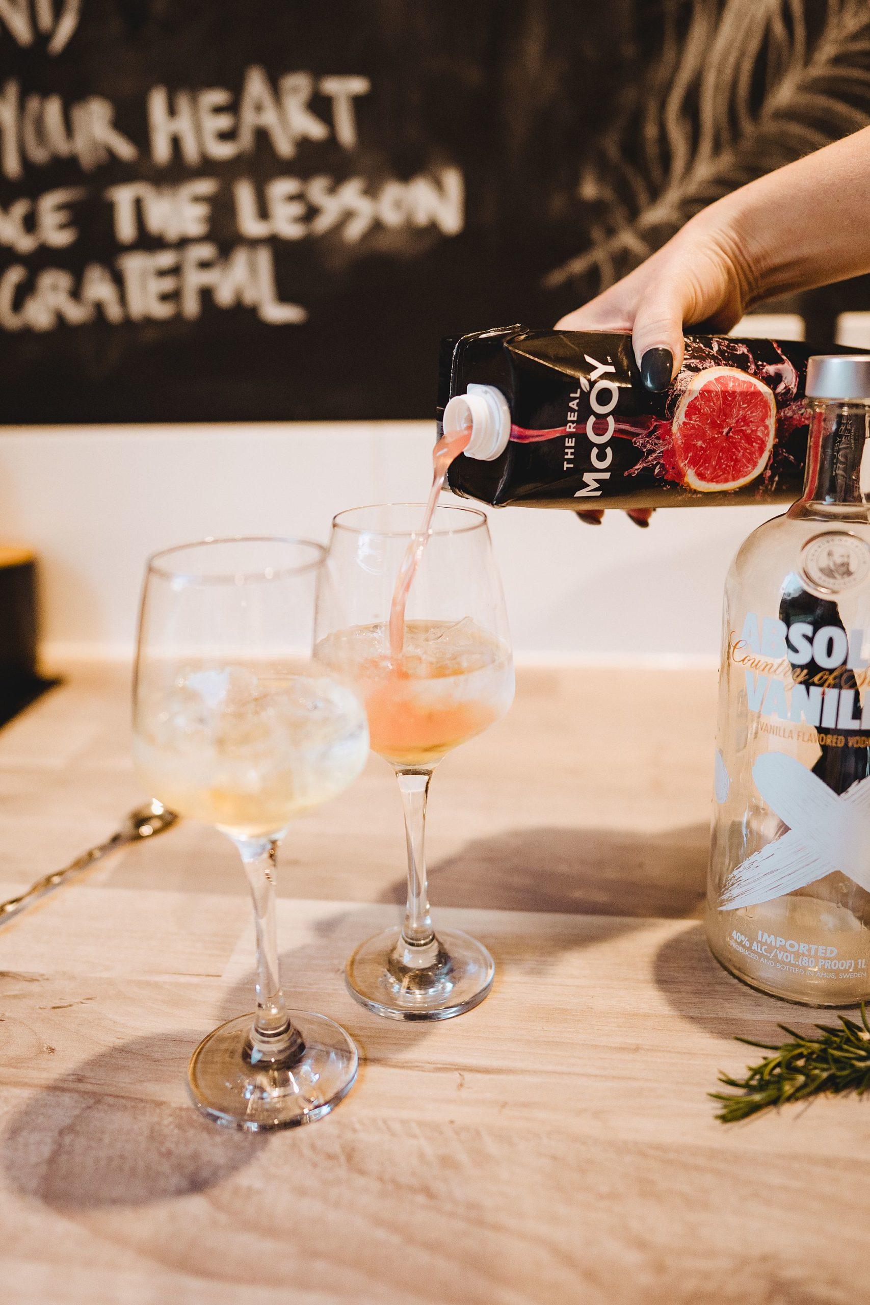 pouring grapefruit juice to vodka cocktail