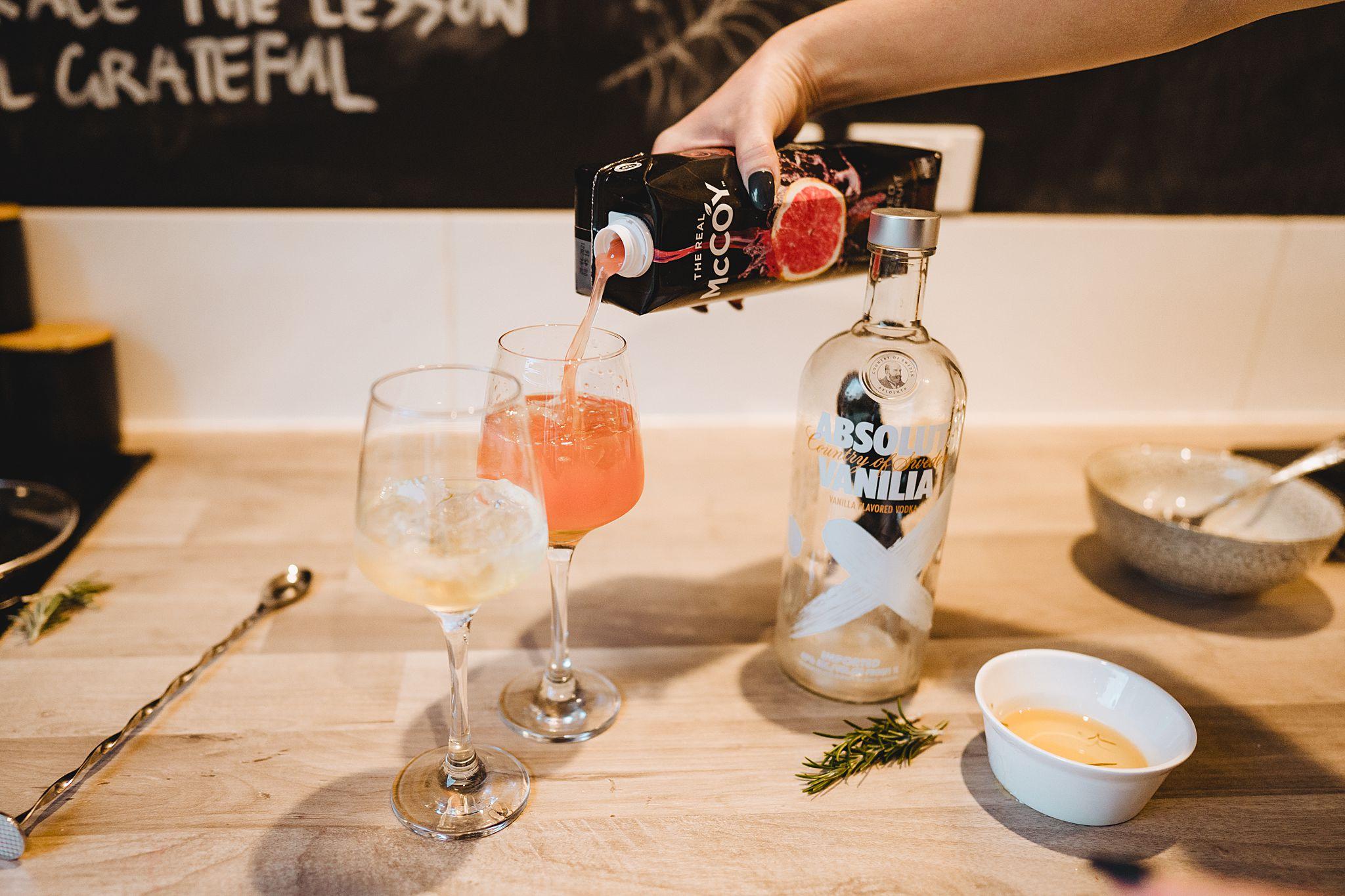 pouring grapefruit juice into vodka cocktail