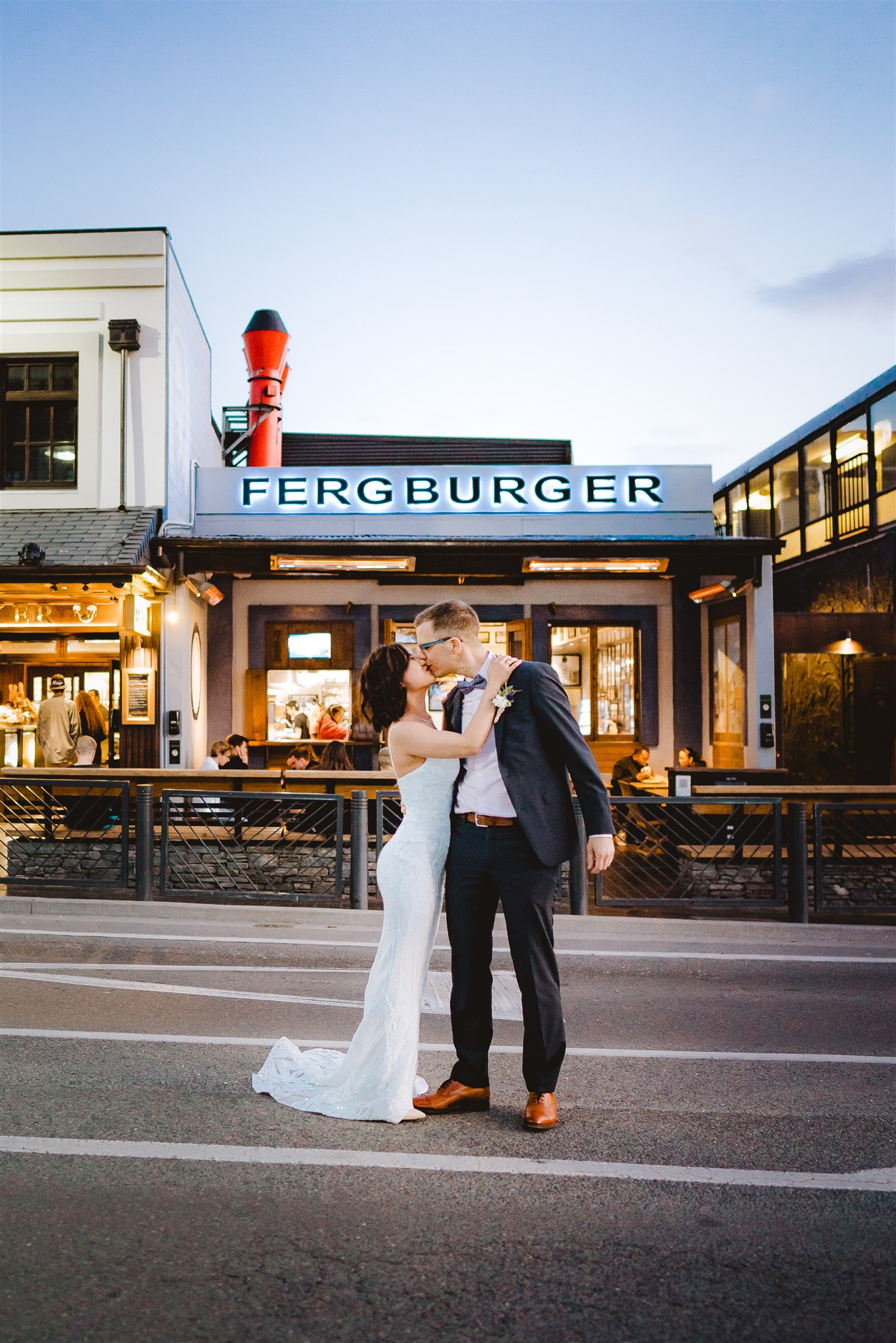 Queenstown wedding couple outside Fergburger Queenstown in wedding dress and wedding suit kissing