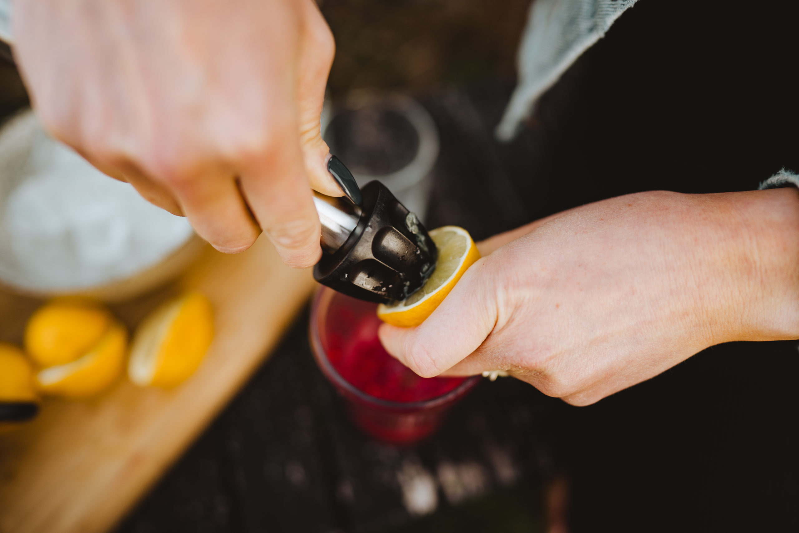 squeezing lime juice into raspberry mojito cocktail