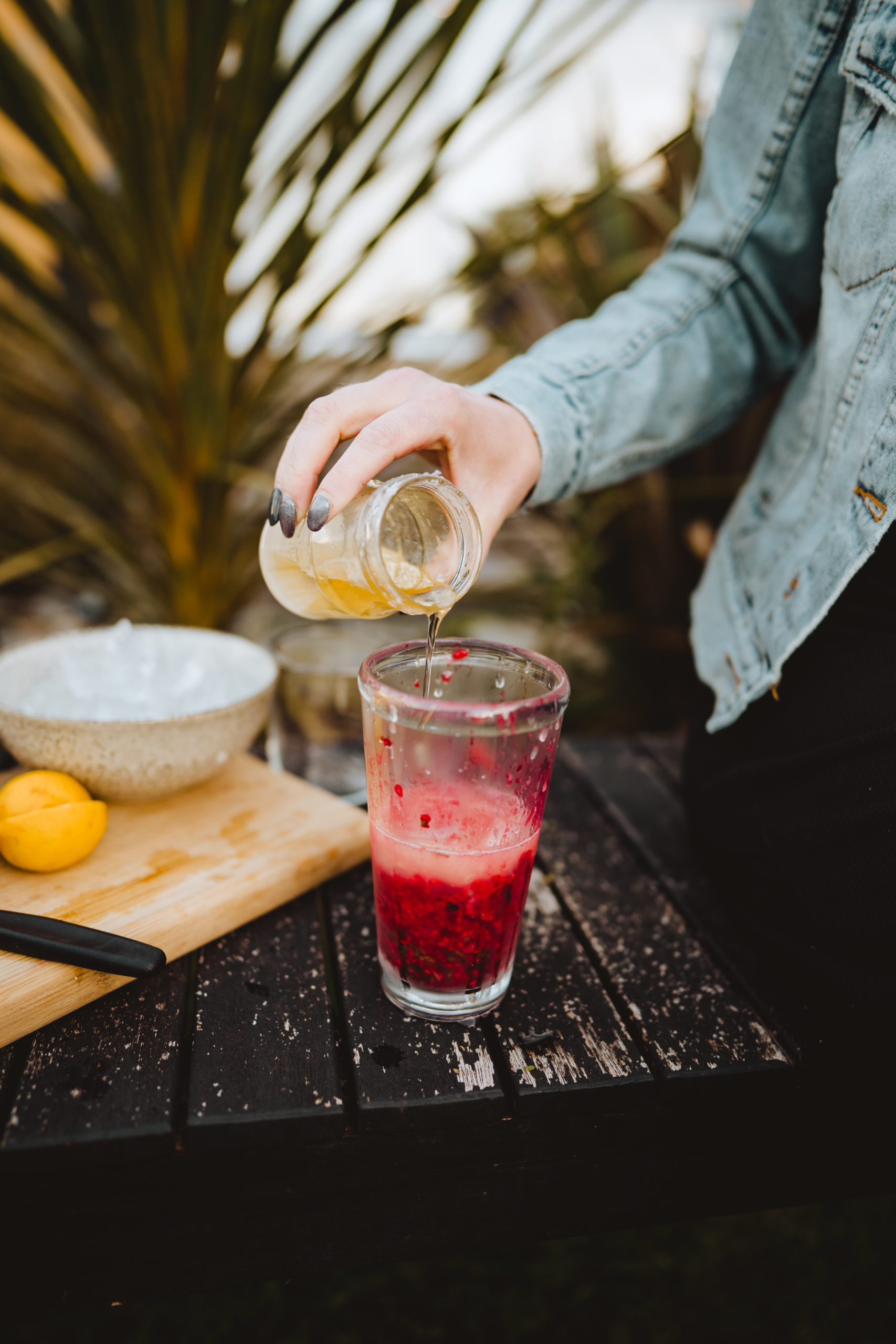 adding sugar syrup to raspberry mojito cocktail