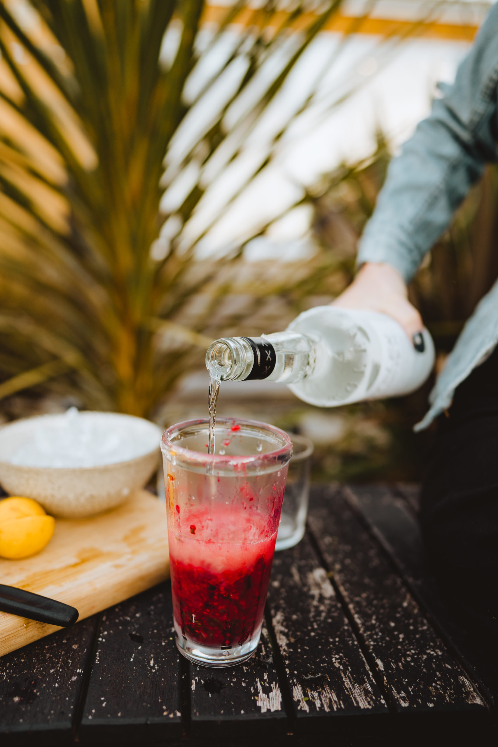 adding rum to raspberry mojito cocktail
