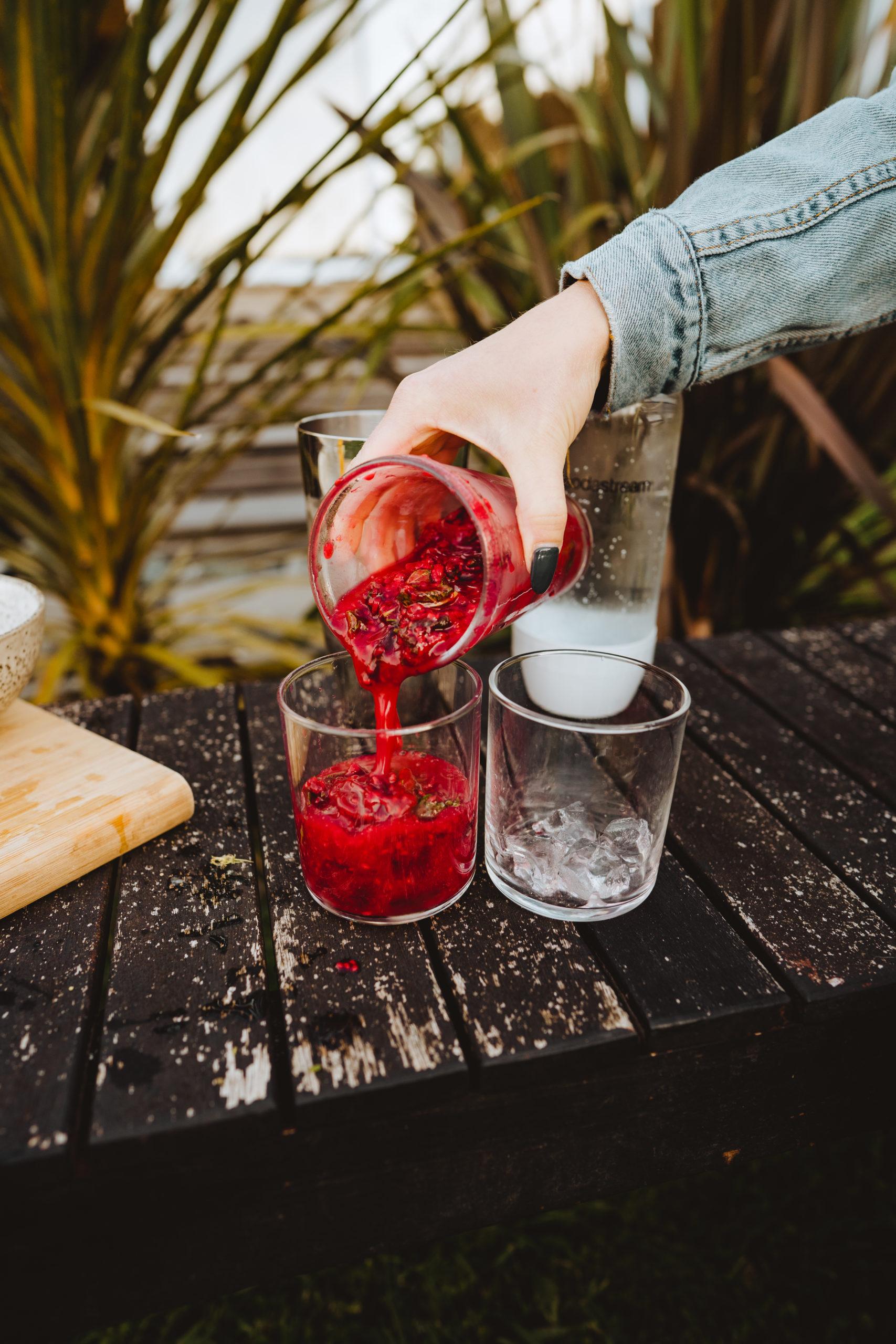 pouring raspberry mojito cocktail into glasses