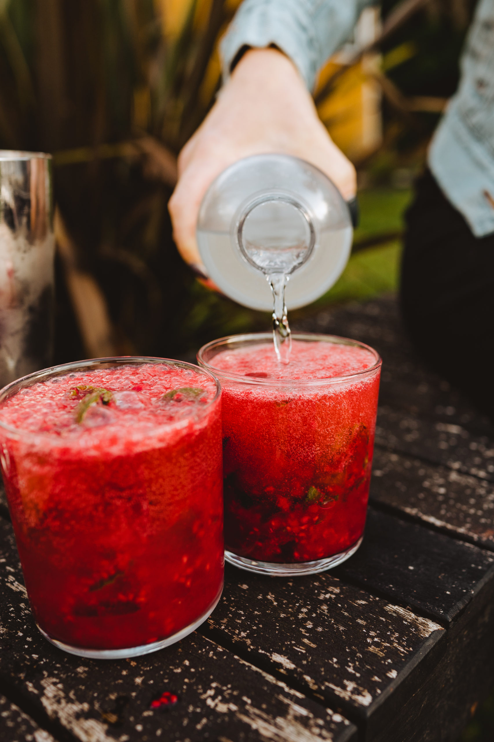 adding sparkling water to raspberry mojito cocktail
